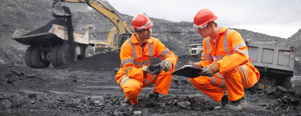 iMINCO training carry out risk management processes - underground mine worker inspecting machinery
