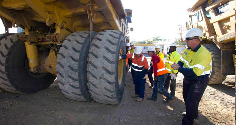 Mining training haul truck course students on site inspecting rear tyres